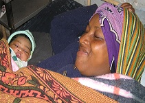 Malagasy mother resting and enjoying her newborn baby just after delivery