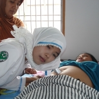 Indonesian midwife listens. Inset: Midwives in Afghanistan. (Photos courtesy of Jhpiego.)