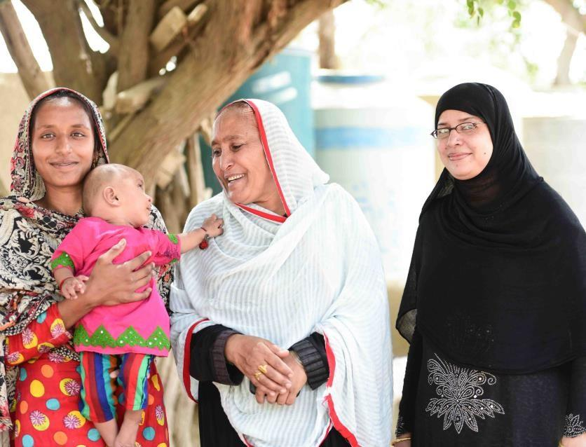Kausar and her daughter with Lady Health Worker Sehat Panwar and Saiqa Moosa, a skilled birth attendant, outside Mithani RHC